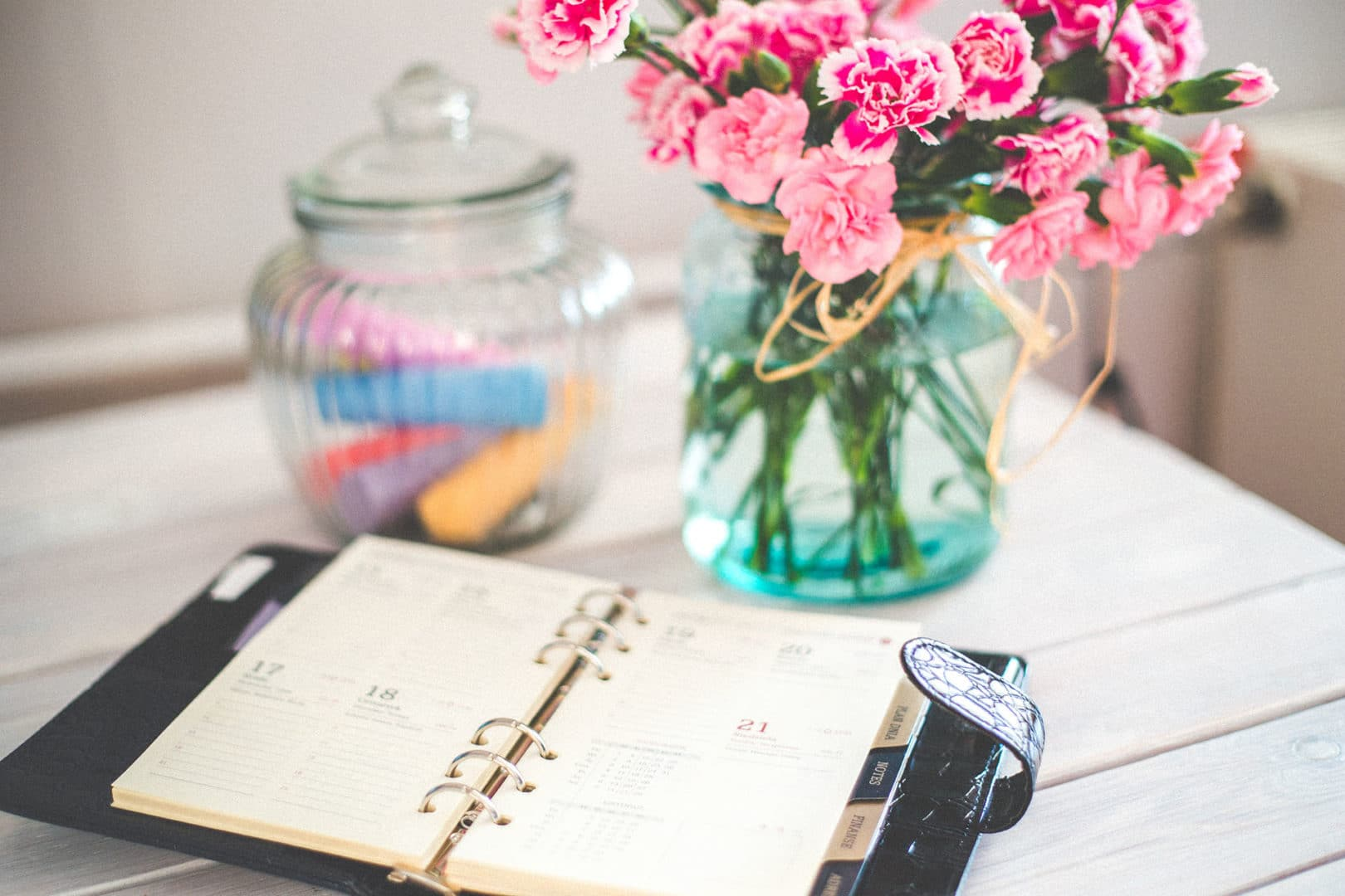 Ein Kalender vor einem Blumenstrauß